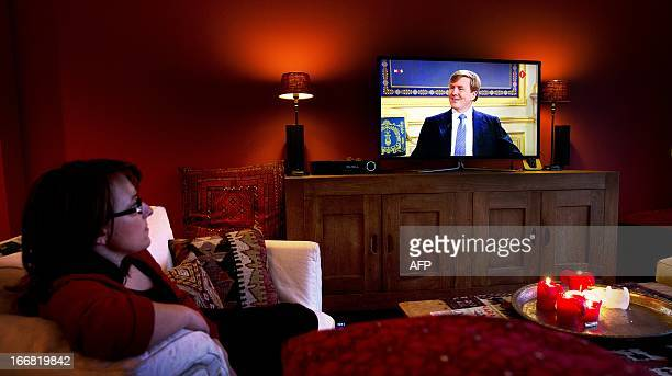 A woman watches a broadcasted interview with Prince WillemAlexander at her home in Rotterdam on April 17 2013 The royal couple was interviewed by...