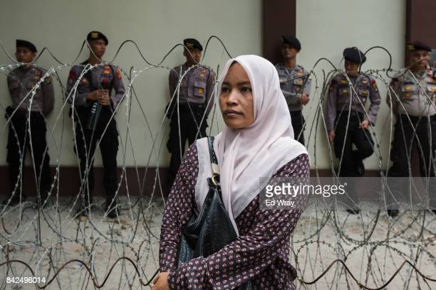 A woman watches a demonstration by hundreds of members of a group calling themselves friends of Muslim Rohingya during a rally by the women's group...