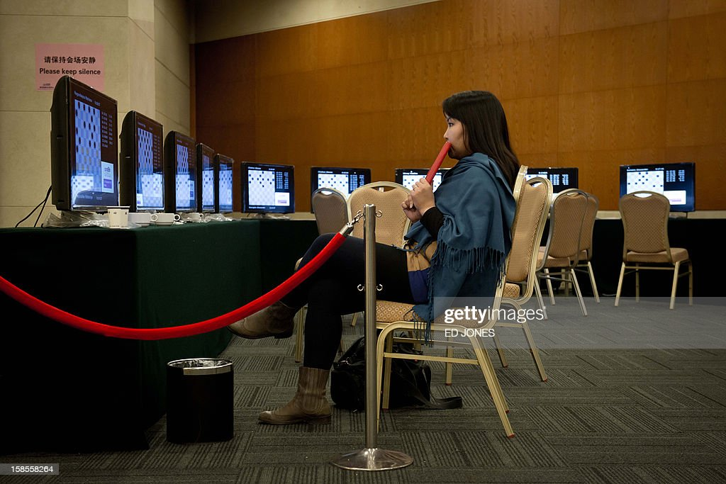 A woman watches a feed showing a 'blinfold' chess tournament at the Beijing 2012 World Mind Games Tournament in Beijing on December 19, 2012. Some of the world's top chess players went eye-to-eye in the year's highest-level 'blindfold' chess tournament -- seen by some as the toughest challenge in the game. Unable to physically see their own or their opponent's past moves, the players summoned headache-inducing levels of concentration to fight for gold in a silent conference room, lined up in front of laptop screens showing a blank board. AFP PHOTO / Ed Jones