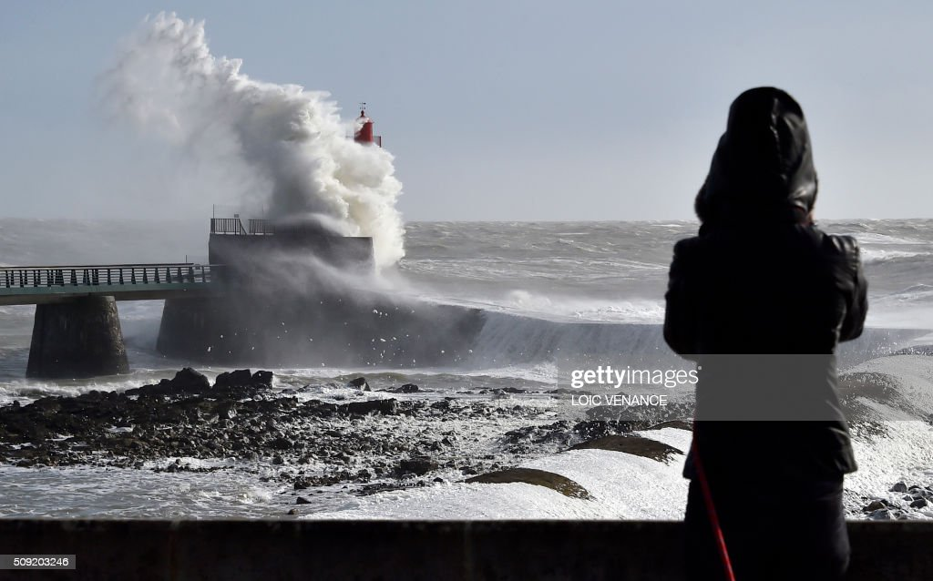A woman watches a wave breaking at a lighthouse in Les Sables-d'Olonne, western France, on February 9, 2016. High winds buffeted northwestern Europe on February 8, leaving one woman in France in a coma after she was hit by an advertising hoarding. Electricity was cut to 5,000 homes in northern France. / AFP / LOIC VENANCE