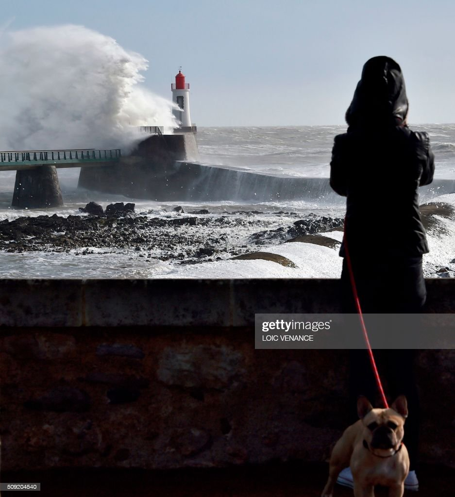 A woman watches a wave breaking at a pier in Les Sables-d'Olonne, western France, on February 9, 2016. High winds buffeted northwestern Europe on February 8, leaving one woman in France in a coma after she was hit by an advertising hoarding. Electricity was cut to 5,000 homes in northern France. / AFP / LOIC VENANCE