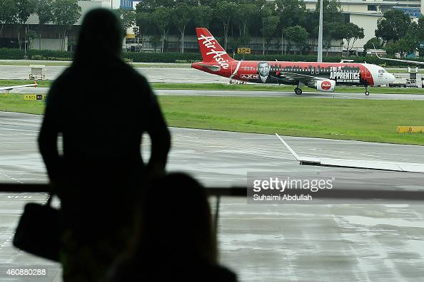 A woman watches an AirAsia plane taxi from the viewing gallery at Changi Airport Terminal 1 on December 29 2014 in Singapore AirAsia announced that...
