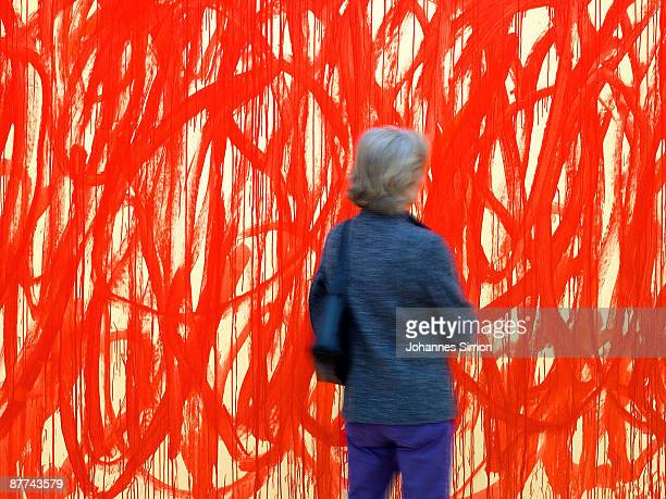 A woman watches an informal painting of artist Cy Twombly during the preview of new built Brandhorst museum on May 18 2009 in Munich Germany The...