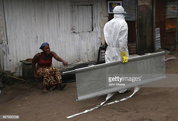 A woman watches as an Ebola burial team arrives to take away her sister Mekie Nagbe for cremation on October 10 2014 in Monrovia Liberia Nagbe a...