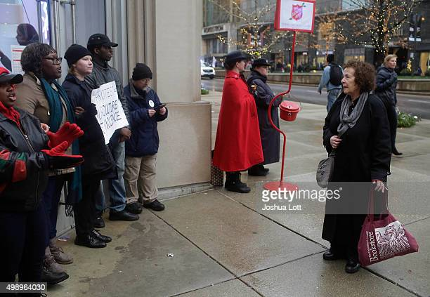 A woman watches as demonstrators block the entrance of the Gap store as they protest the shooting of Laquan McDonald who was killed by a Chicago...