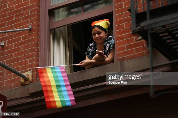 A woman watches as participants in the annual New York Gay Pride Parade one of the oldest and largest in the world march throughthe West Village in...