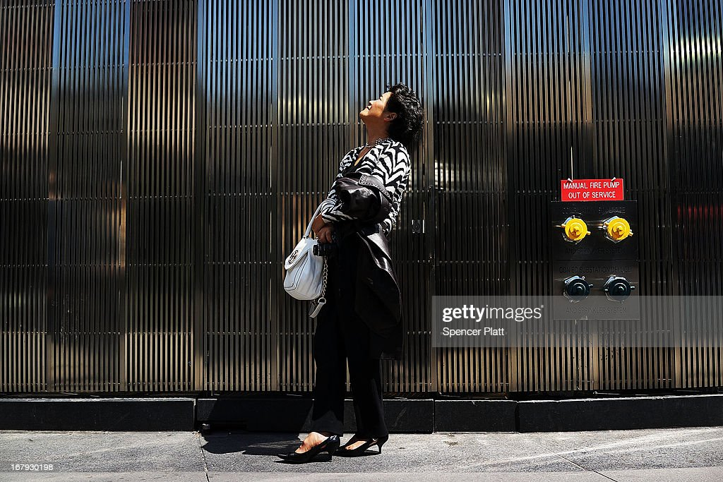 A woman watches as the last 75-foot section of the 408-foot spire is hoisted onto a temporary platform on the top of One World Trade Center on May 2, 2013 in New York City. When bolted into place at a later date, the spire will make One World Trade Center the tallest building in the Western Hemisphere.The raising of the spire, which comes on the second anniversary of the death of Osama bin Laden, will make One World Trade Center 1,776 feet tall. One World Trade Center is built on the site where the September 11, 2001 attacks toppled the original World Trade Center towers.