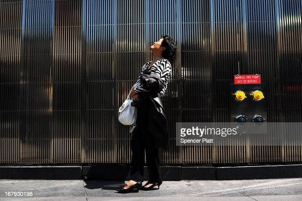 A woman watches as the last 75foot section of the 408foot spire is hoisted onto a temporary platform on the top of One World Trade Center on May 2...