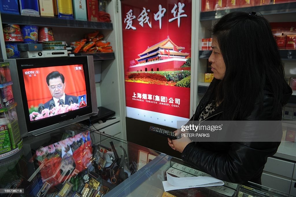 A woman watches Chinese President Hu Jintao speaking at the opening of the 18th Communist Party Congress on television in her cigarette shop in Shanghai on November 8, 2012. Chinese President Hu Jintao called for stepped-up political reform and a revamped economic model as the Communist Party opened a historic congress to usher in a new slate of leaders. AFP PHOTO/Peter PARKS.
