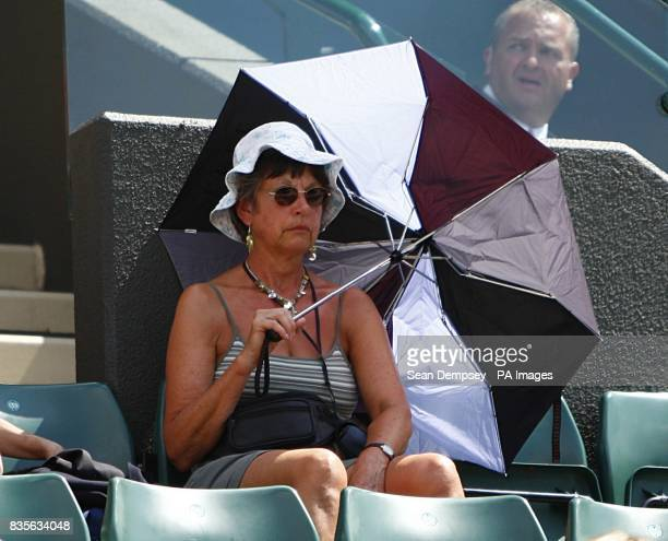 A woman watches Czech Republic's Tomas Berdych against Russia's Nikolay Davydenko on Court One from the shelter of her umbrella during the Wimbledon...