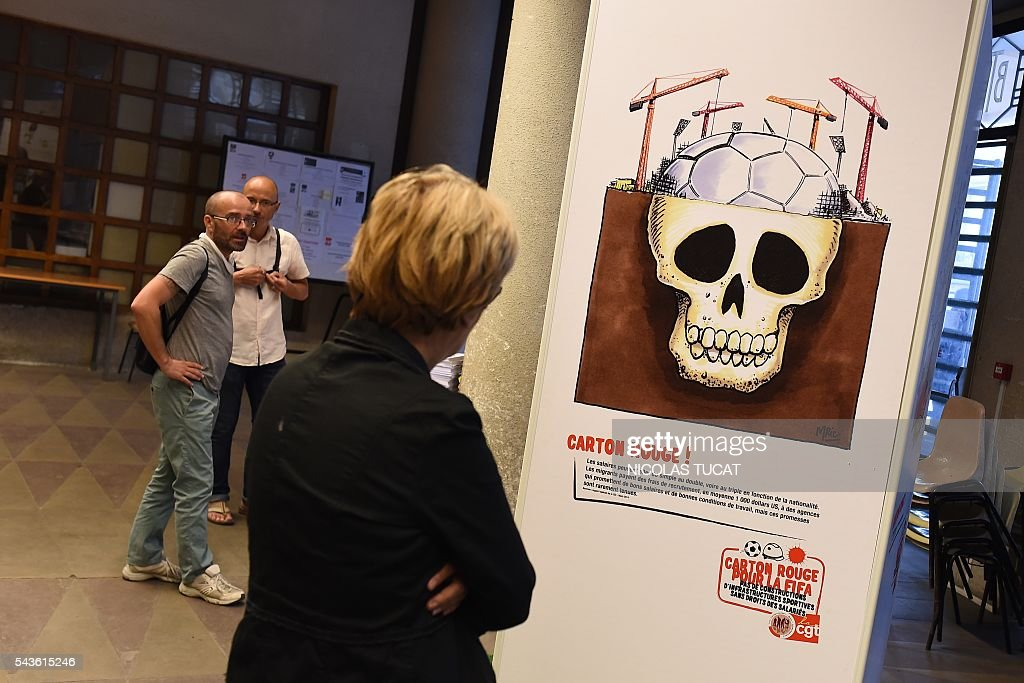 A woman watches drawings of the 'Carton rouge a la FIFA' (A red card for the International Football Federation) exhibition on June 29, 2016 in Bordeaux, southwestern France. This exhibition by French General Confederation of Labour (CGT) workers union focuses on the exploitation of workers on the construction sites of major international competitions such as Quatar or Russia. / AFP / NICOLAS