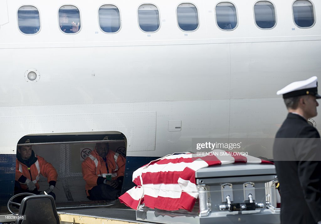 A woman watches from a window as ground crew wait for a US Navy transfer team to carry a casket with the remains of a US Civil War casualty from Delta Flight 1172 during a dignified transfer at Dulles International Airport on March 7, 2013 in Sterling, Virginia. The remains of two unknown soldiers found inside the sunken iron clad ship, the USS Monitor, were transfered for burial at Arlington National Cemetery after being discovered in 2002 and being sent to Joint POW/MIA Accounting Command in Hawaii for possible genetic identification. AFP PHOTO/Brendan SMIALOWSKI