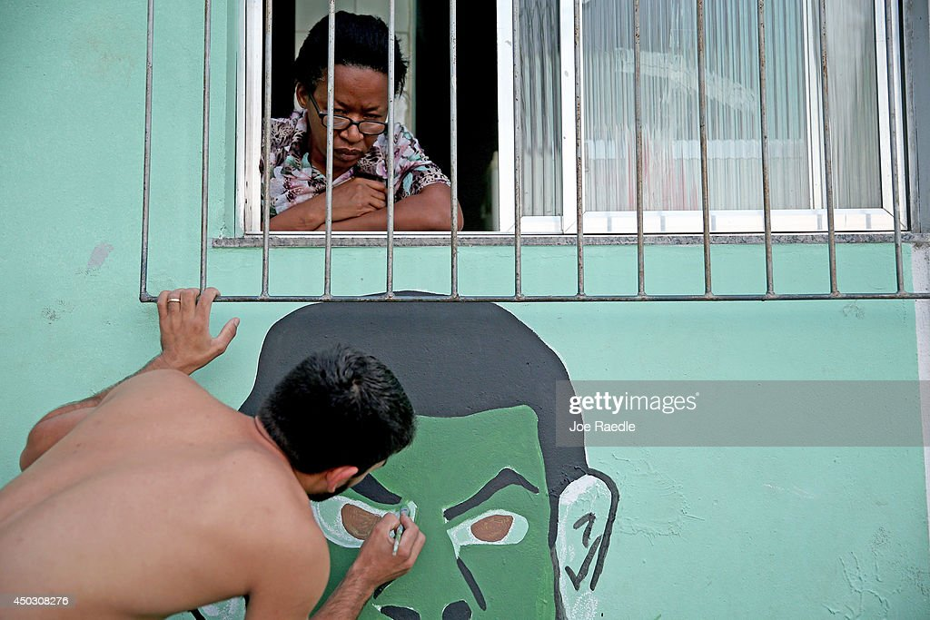 A woman watches from her window as a young man paints a World Cup mural on the street and the wall of her apartment in a 'favela' called Santa Marta as they prepare for the start of World Cup play on June 8, 2014 in Rio de Janeiro, Brazil. Brazil continues to prepare to host the World Cup which starts on June 12th and runs through July 13th.