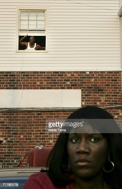 A woman watches from the street while a man looks down from his window during the Black Men of Labor Annual Labor Day Parade September 3 2006 in New...