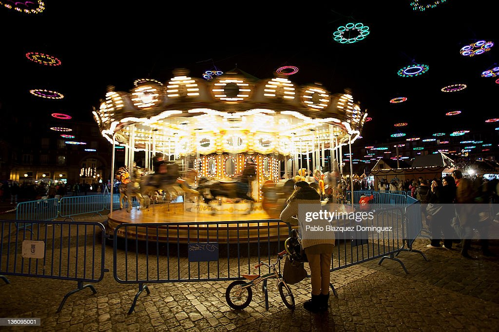 A woman watches her children ridding in a festive Merry-go-round in a Christmas market fair at Plaza Mayor Square six days before Christmas Day on December 19, 2011 in Madrid, Spain. This year businesses are starting sales and discounts before Christmas to try and gain customers during the current economic crisis.