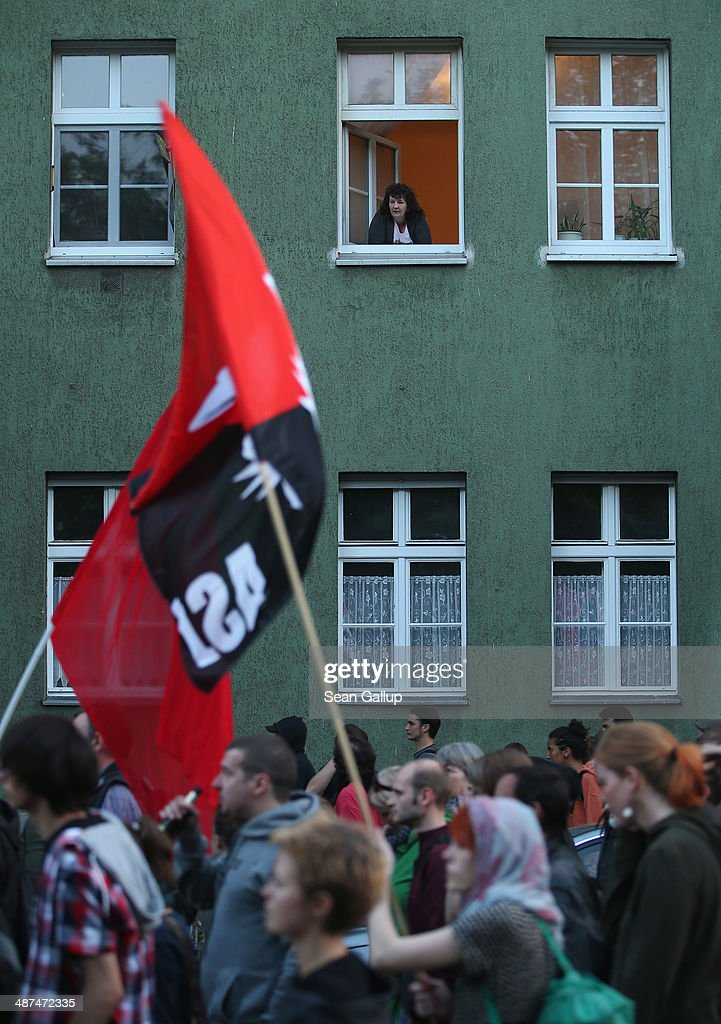A woman watches leftist protesters march by in the 'AntiCapitalist Walpurgis Night' demonstration in Wedding district on April 30 2014 in Berlin...