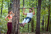 Woman watches man doing exercises on high bars in forest gym