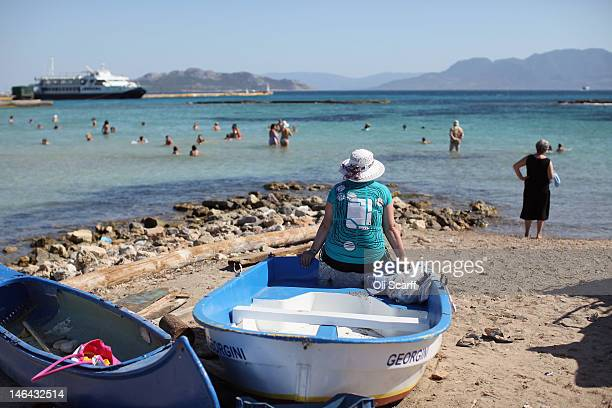 A woman watches people play in the sea of the island of Aegina on June 16 2012 in Aegina Greece The Greek electorate are due to go to the polls...
