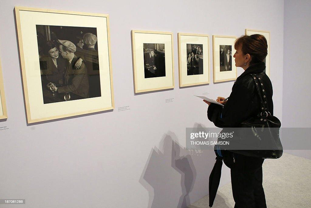 A woman watches photographs of Brassai during the exhibition entitled 'Brassai, pour l'amour de Paris' ('Brassai, for the love of Paris') at the Hotel de Ville of Paris, on November 6, 2013. AFP PHOTO THOMAS SAMSON