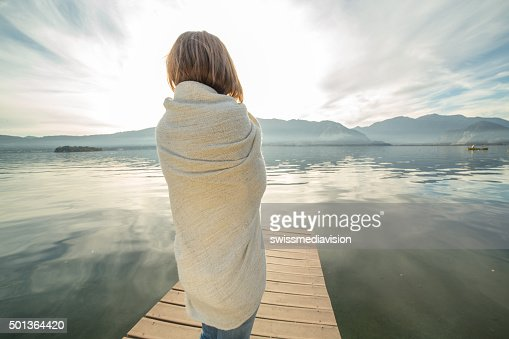 Woman watches sunset from lake pier, wrapped in blanket