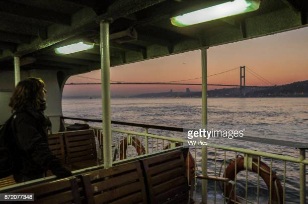 A woman watches the Bosphorus bridge from a ferry boat at sunset
