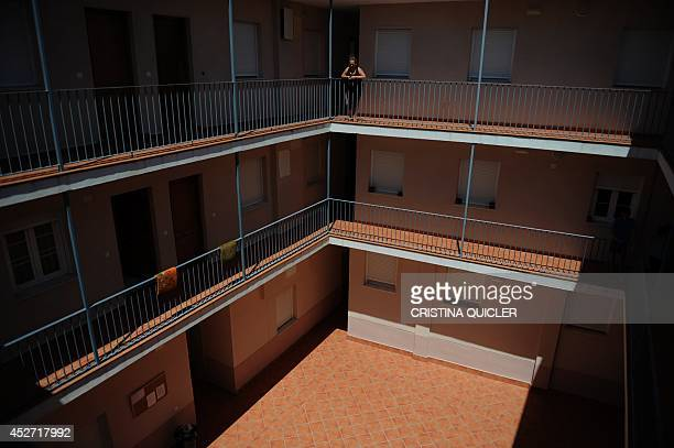 A woman watches the empty patio of the occupied building Jaramillo Corrala in Sanlucar de Barrameda near Cadiz on July 27 2014 Some 80 families...