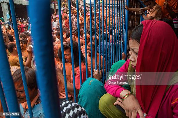 A woman watches the festival from behind an iron fence during the Sindoor Jatra Festival on April 15 2015 in Thimi Nepal Sindoor Jatra Festival is...