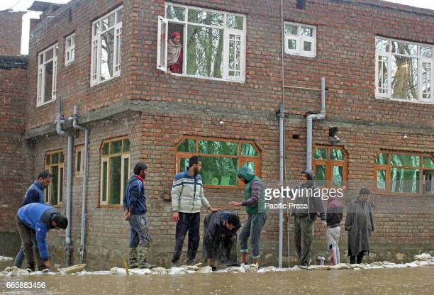 A woman watches the flooded area around them from the window of their house in Srinagar Indiancontrolled Kashmir Friday April 7 2017 Six people...