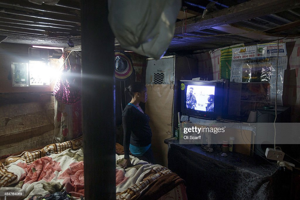 A woman watches the official memorial service for Nelson Mandela on a television inside her makeshift home in Alexandra Township on December 10, 2013 in Johannesburg, South Africa. Over 60 heads of state have travelled to South Africa to attend a week of events commemorating the life of former South African President Nelson Mandela. Mr Mandela passed away on the evening of December 5, 2013 at his home in Houghton at the age of 95. Mandela became South Africa's first black president in 1994 after spending 27 years in jail for his activism against apartheid in a racially-divided South Africa.