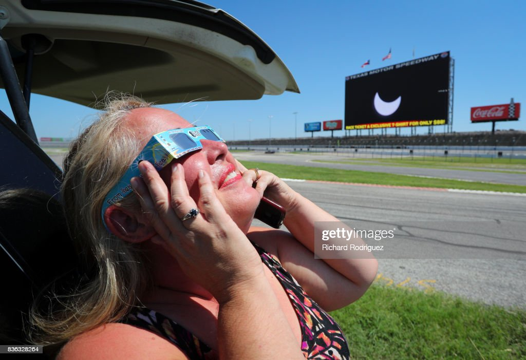 A woman watches the solar eclipse at Texas Motor Speedway on August 21, 2017 in Fort Worth, Texas. Millions of people have flocked to areas of the U.S. that are in the 'path of totality' in order to experience a total solar eclipse. During the event, the moon will pass in between the sun and the Earth, appearing to block the sun. Fort Worth residents will see about 75 percent of the sun blocked by the moon.