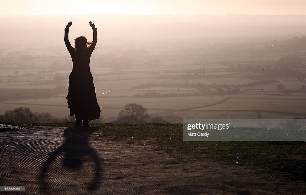 A woman watches the sun rise during Beltane dawn celebration service in front of St. Michael's Tower on Glastonbury Tor on May 1, 2013 in Glastonbury, England. Although more synonymous with International Workers' Day, or Labour Day, May Day or Beltane is celebrated by druids and pagans as the beginning of summer and the chance to celebrate the coming of the season of warmth and light. Other traditional English May Day rites and celebrations include Morris dancing and the crowning of a May Queen with celebrations involving a Maypole.