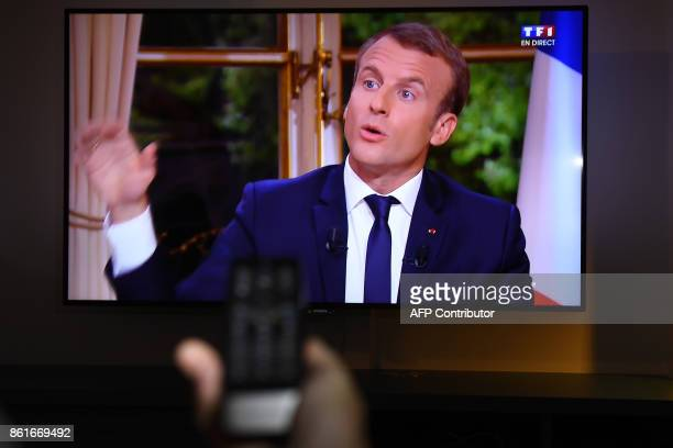 A woman watches the television interview of France's President Emmanuel Macron as he takes part in the broadcast news of TF1 on October 15 2017 in...