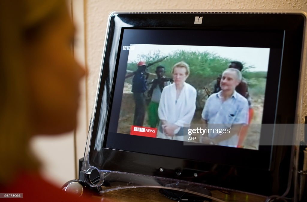 A woman watches video footage on November 21 2009 of the British couple that were kidnapped while sailing off the coast of Somalia Paul and Rachel...