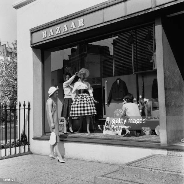 A woman watches windowdressers at work at the 'Bazaar' boutique in Chelsea London