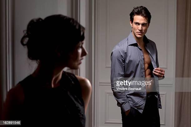 A woman watching a man undressing