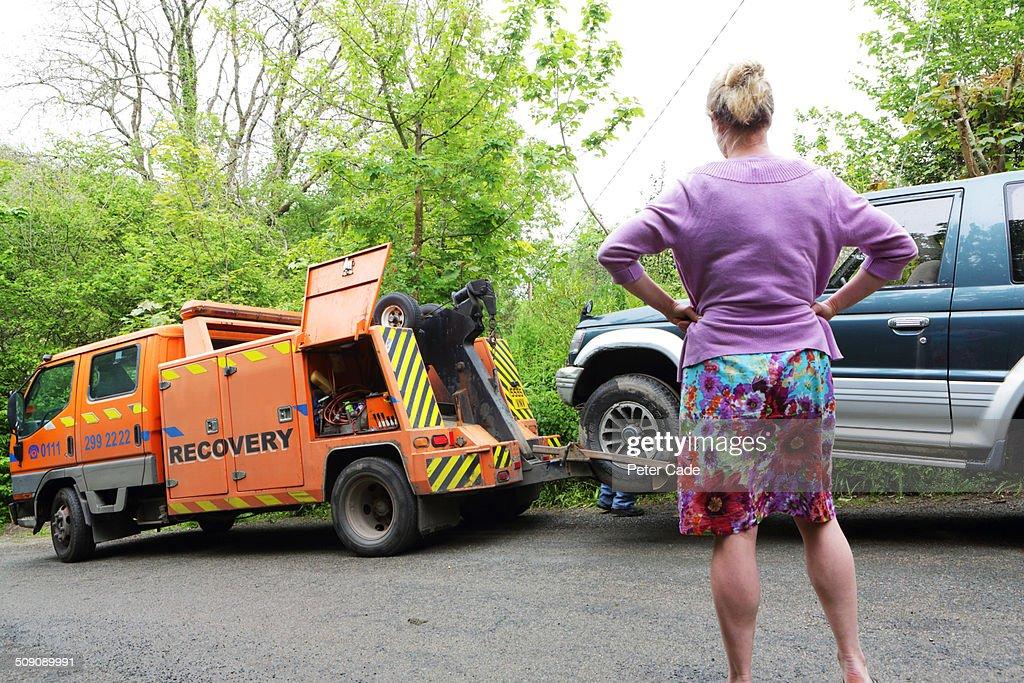 Woman watching as broken down car is towed away