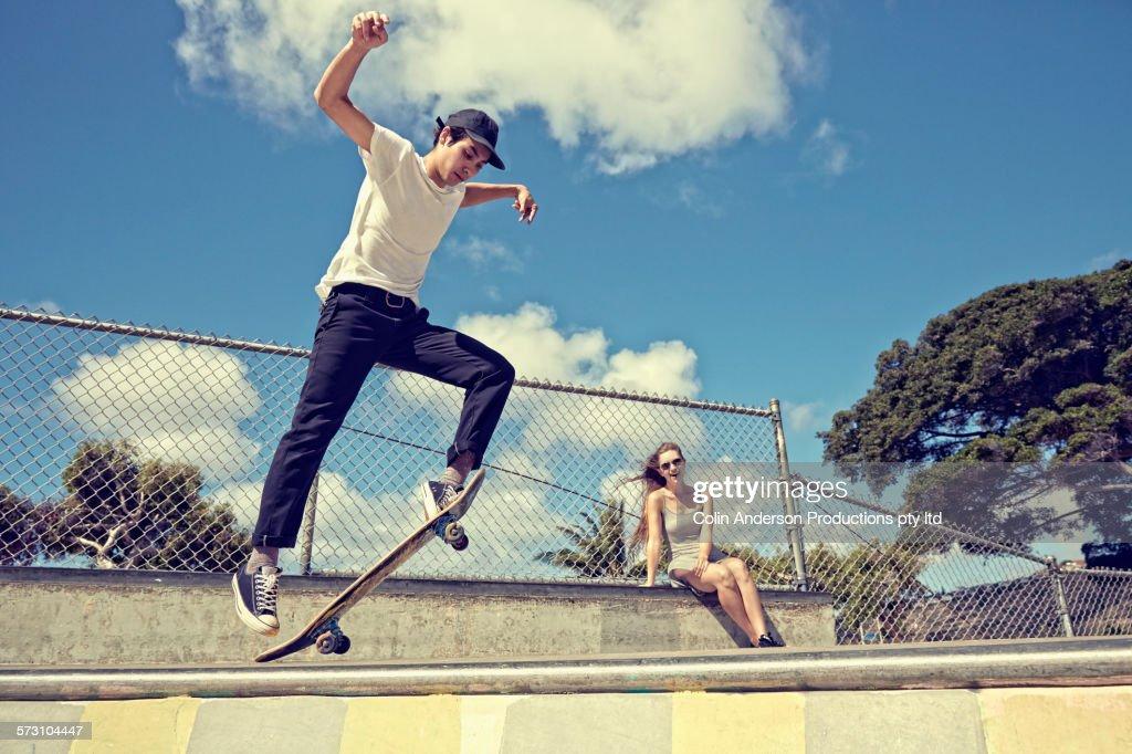 Woman watching boyfriend perform trick at skate park