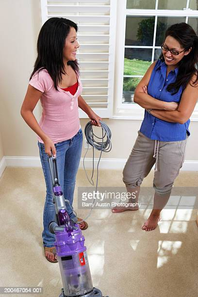 Woman watching daughter (13-15) use vacuum cleaner, smiling