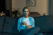 portrait of smiling woman with popcorn watching film at home