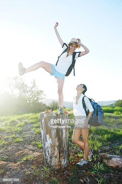 Woman watching friend balancing on dilapidated stump