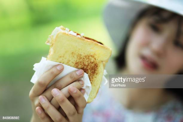 woman watching hand holding bread
