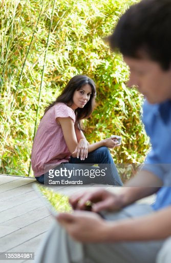 Woman watching husband use digital tablet on patio : Stock Photo
