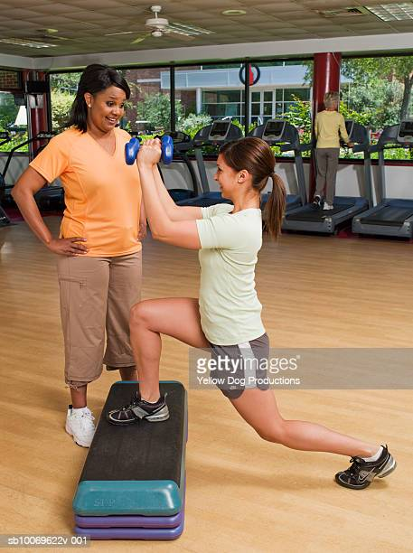 Woman watching instructor exercise in health club