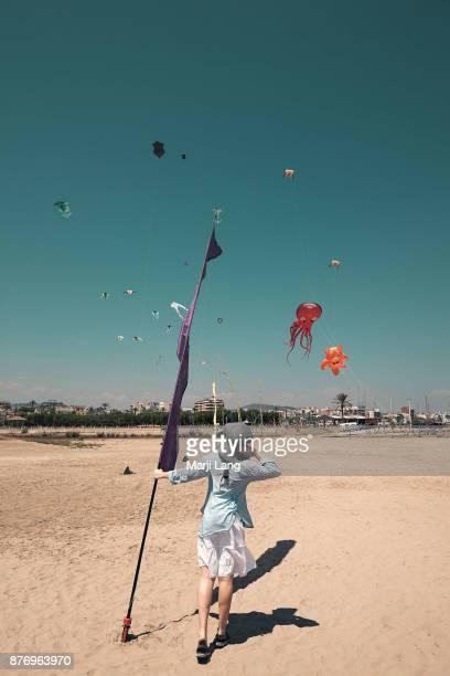 Woman watching kites in the windy blue sky above the beach in Vilanova I la Geltru near Barcelona Spain