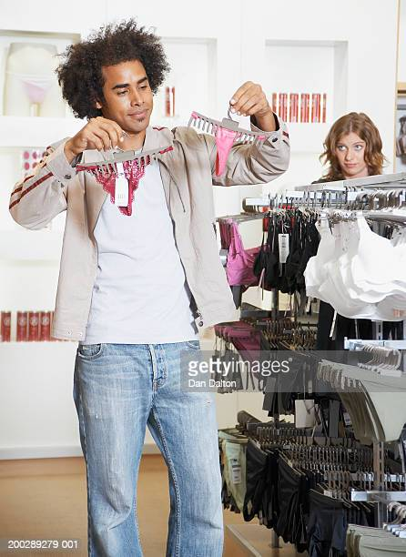 Woman watching man hold up g-strings on hangers in shop