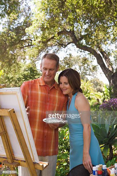 Woman watching man while he paints