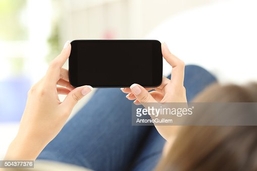 Woman watching media in a smart phone : Stock Photo