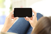 Back view of a close up of a woman hands watching media in a smart phone lying on a couch at home