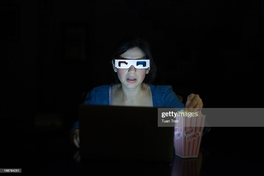 Woman watching movies on laptop with 3D glasses : Stock Photo