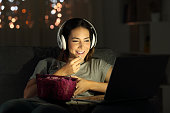 Single woman watching online tv in the night sitting on a couch in the living room at home